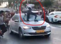 צפו: מפגינים מטפסים על רכב נוסע וחובטים בו