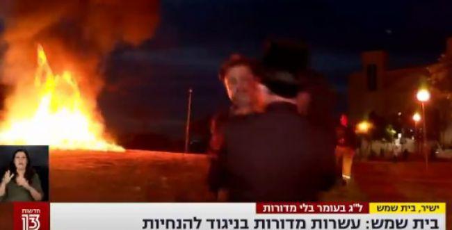 בשידור חי: כתב ערוץ 13 הותקף בהדלקת מדורה