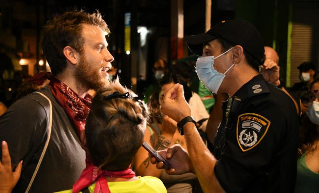 """ההפגנות בת""""א: 3 עצורים, מפגינה הכתה שוטר בפניו"""