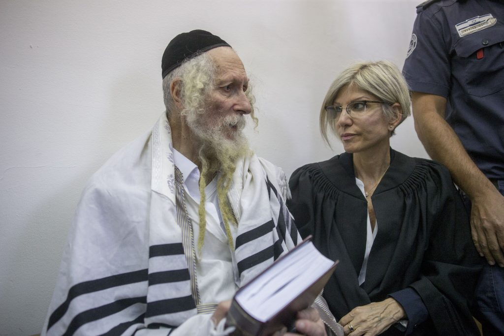 Rabbi Eliezer Berland covers himself with his talit (prayer shawl) at the District court in Jerusalem as he is put on trial for sexual assualt charges, on August 1, 2016. Rabbi Berland left Israel to South Africa while he was suspected and under investigation for sexual assualt on women in his community. He was jailed in South Africa and extradited to Israel. Photo by Yonatan Sindel/ Flash90 *** Local Caption *** תפילה בית משפט דרום אפריקה הרב אליעזר ברלנד רב כלא אונס