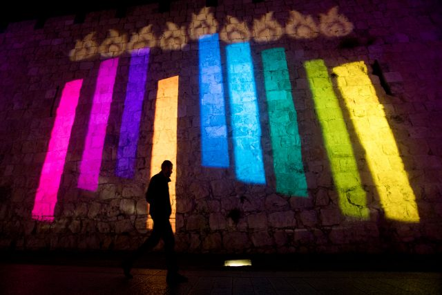 Pepole walk past the walls of Jerusalem's Old City illuminated with projection showing Menorah and Dreidels during the Jewish holiday of Hanukkah on December 24, 2016, Hanukkah, also known as the Festival of Lights, is an eight-day Jewish holiday commemorating the rededication of the Holy Temple. The festival is observed by the kindling of the lights of a 'hanuckia'- a nine-branched candelabrum, with one additional light being lit on each night of the holiday. Photo by Yonatan Sindel/Flash90 *** Local Caption *** çðåëä çðåëééä îðåøä ðøåú éøåùìéí çøãé çøãéí çåîåú äòéø äòúé÷ä òéø òúé÷ä ä÷øðä